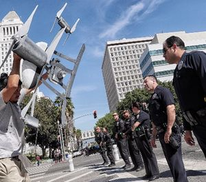 Miguel Guzman flaunts a drone replica in front of Los Angeles Police Department officers after a group blocked downtown traffic, protesting the the LA Police Commission vote to allow the LAPD to use drones, on Tuesday, Oct. 17, 2017. (Robert Gauthier/Los Angeles Times/TNS)