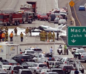 Emergency responders gather round the crash of a Cessna 310 aircraft on Interstate 405. (AP Photo/Chris Carlson)