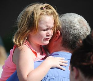 Lilly Chapman, 8, cries after being reunited with her father, John Chapman at Oakdale Baptist Church on Wednesday, Sept. 28, 2016, in Townville, S.C. Students were evacuated to the church following a shooting at Townville Elementary School. (AP Photo/Rainier Ehrhardt)