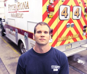 """Paramedic Ross Williams is photographed in the Fitchburg Fire Department garage. Williams is the one who gained Andrew's trust and carried him down the stairs at the Oneida Street house seven years ago. Andrew, which is no longer his name, remembers Williams. """"That's an honor,"""" Williams said. (Image Portage Daily Register)"""
