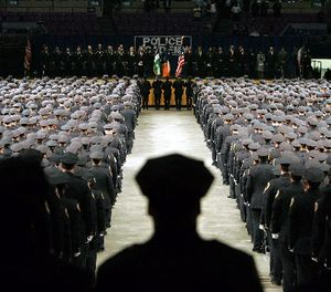 In this file photo of July 13, 2005, New York City Police Academy graduates stand at attention during the presentation of colors at Madison Square Garden in New York. (AP Photo/Julie Jacobson, File)