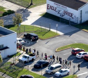 Students are evacuated by police from Marjory Stoneman Douglas High School in Parkland, Fla., on Wednesday, Feb. 14, 2018, after a shooter opened fire on the campus. (Mike Stocker/South Florida Sun-Sentinel via AP)