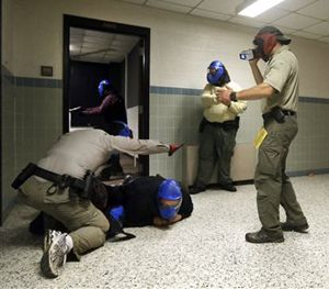 In this Aug. 13, 2013 photo, FBI instructor Mike Sotka, center, films local officers as they participate in an active shooter drill in a college classroom building in Salisbury, Md. (AP Image)