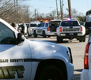 Law enforcement personnel from the Ellis County Sheriff's Office park outside a high school in Italy, Texas, following an active shooter incident at the school Monday morning, Jan. 22, 2018. (Jennifer Lindgren/KTVT Dallas Fort Worth via AP)