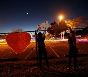 A student at Marjory Stoneman Douglas High School hangs signs on the fence of the school. (Photo/AP)