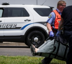 Emergency personnel carry a volunteer to a triage staging area during a training exercise for an active shooter with simulations at Hopewell Elementary School, Wednesday, May 25, 2016, in West Chester, Ohio. (AP Photo/John Minchillo)