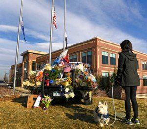 With flags at half staff, Maribeth Forst, with her dog Max, stands near a makeshift memorial on a police cruiser for the victims of what authorities describe as an ambush Monday, Jan. 1, 2018, at the Douglas Country Sheriff Substation in Highlands Ranch, Colo. (Helen H. Richardson/The Denver Post via AP)