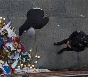 An NYPD officer stands by a memorial Sunday, Dec. 21, 2014, honoring two New York Police Department officers who were shot while sitting inside a patrol car nearby the previous day. (AP Image)