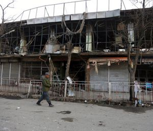 A member of Afghan security forces walks past the site of Saturday's suicide attack in Kabul, Afghanistan. (Photo/AP)