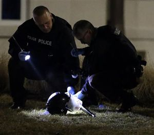 Police shine a light on a helmet as they investigate the scene where two police officers were shot outside the Ferguson Police Department Thursday, March 12, 2015, in Ferguson. (AP Image)