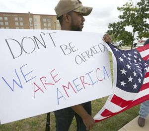 Joseph Offutt, left, and Raheem Peters hold a sign and a U.S. flag across the street from the Curtis Culwell Center, Tuesday, May 5, 2015, in Garland, Texas. (AP Image)