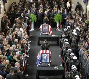 Jamal Knox's rap song's lyrics contained a reference to Richard Poplawski who murdered three Pittsburgh officers in 2009. In this April 8, 2009, file photo family and officials pay their respects to those three Pittsburgh police officers. (AP Photo/Gene J. Puskar, File)