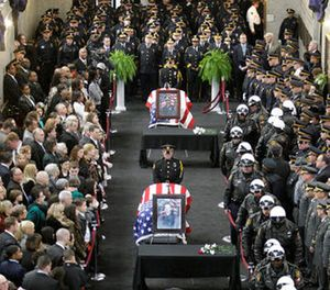 In this April 8, 2009 file photo family and officials pay their respects to the three Pittsburgh officers who were shot and killed while responding to a 911 call in Pittsburgh. (AP Photo/Gene J. Puskar, File)