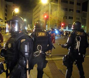 In this March 30, 2014 file photo, riot police stand guard near a crowd protesting police shootings in Albuquerque, N.M. (AP Image)