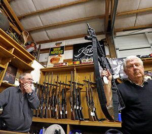 In this Oct. 20, 2017, file photo, sales clerk Tom Wallitner holds up a Mossberg 715T .22-caliber semi-automatic rifle during an auction at Johnny's Auction House, where the company handles gun sales for a half dozen police departments and the Lewis County Sheriff's Office, in Rochester, Wash. (AP Photo/Elaine Thompson, File)