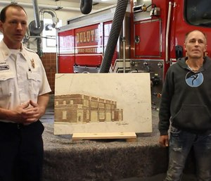 Artist Eric Waller presented Duluth Fire Department staff with a relief depicting the fire station carved into a slab of white Italian Carrara marble. (Photo/Duluth News Tribune)