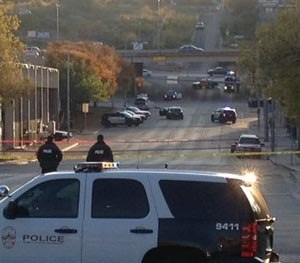 Police tape marks off the scene after authorities shot and killed a man who they say opened fire on the Mexican Consulate, police headquarters and other downtown buildings early Friday, Nov. 28, 2014, in Austin, Texas. In the distance, police cars surround the suspect's vehicle parked near the Interstate 35 overpass. (AP Image)