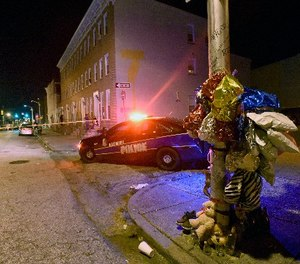 A previously created memorial, right, stands as Baltimore police work at a scene where multiple people were shot in Baltimore, Saturday night, Sept. 24, 2016. (AP Photo/Steve Ruark)