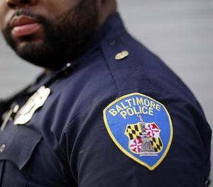 In this March 31, 2016 photo, a Baltimore Police Department officer stands on a street corner during a foot patrol. (AP Image)