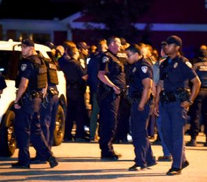 In this Monday, Nov. 13, 2017, photo, law enforcement officers stand ready when a crowd gathers as Louisiana State Police investigate the scene where a Baton Rouge Police officer fatally shot a man during a struggle at The Palms Apartments in Baton Rouge, La. (Patrick Dennis/The Advocate via AP)