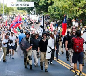 In this Aug. 12, 2017 file photo, White nationalist demonstrators walk through town after their rally was declared illegal near Lee Park in Charlottesville, Va.(AP Photo/Steve Helber, File)