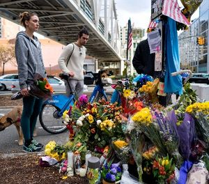 Amy Biden, left, of New York, with her dog Smokey, stands with flowers she brought to a makeshift memorial that that honors victims of an attack who were stuck and killed by a rental truck driven by indicted suspect Sayfullo Saipov Tuesday, at Chambers and West Streets in New York, Saturday, Nov. 4, 2017. (AP Photo/Craig Ruttle)