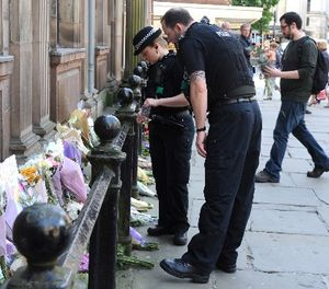Police look at floral tributes left at St Ann's square, Manchester, England Tuesday May 23, 2017. (AP Photo/Rui Vieira)