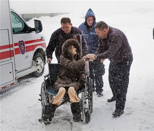 Paramedics wheel a patient into the hospital after driving through a blizzard to reach her. (Michael Beck/Stony Brook Hospital via AP)