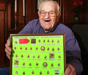 In a March 23, 2017 photo, Harold Facklam displays the many pins he has collected for having donated 32 gallons of blood over more than six decades, in Topeka, Kans. Facklam Jr. (Thad Allton/The Topeka Capital-Journal via AP)