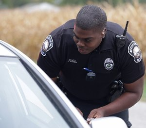 In this file photo taken on Tuesday, Sept. 29, 2015, a body camera is attached to the uniform of Whitestown Police Department officer Reggie Thomas during a traffic stop, in Whitestown, Ind. (AP Photo/Darron Cummings)