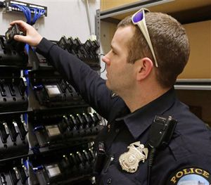 In this Feb. 2, 2015 photo, Duluth, Minn., police officer Dan Merseth demonstrates the docking procedure for police body cameras at police headquarters. (AP Image)