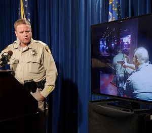 Las Vegas police Undersheriff Kevin McMahill watches body camera footage during a press conference on accusations by Seattle Seahawks player Michael Bennett, Wednesday, Sept. 6, 2017, in Las Vegas. (AP Photo/John Locher)