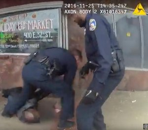 In this image taken from video from a body camera worn by a Baltimore police officer on Monday, Nov. 25, 2016, three officers attend to a man that was shot in Baltimore. The police officers shot the man who was threatening people with knives at a bus stop. (Photo/Baltimore Police Department via AP)