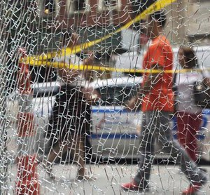 New Yorkers pass a shattered storefront window on W. 23rd St. in Manhattan, Tuesday, Sept. 20, 2016, in New York. (AP Photo/Mark Lennihan)