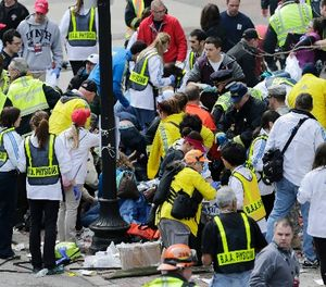 In this Monday, April 15, 2013 file photo, medical workers aid injured people at the finish line of the 2013 Boston Marathon following an explosion in Boston. Over 13,000 videos and 120,000 photos were sent to police during the investigation. (AP Photo/Charles Krupa)