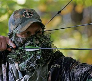 Jim Bruchac takes aim with compound bow and arrow as he demonstrates still hunting techniques used for hunting in Greenfield, N.Y. (AP Image)