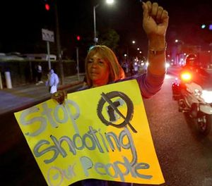 Marian Petersen, 71, whose last protest was in the 1965 Watts riots, marches down Central Avenue to the LAPD's Newton Division station after officers shot a Latino boy Sunday night. (Photo/Los Angeles TImes)