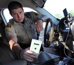 In this Sept. 21, 2015 photo, Minnehaha County Deputy Sheriff Elliott Crayne installs a car breathlyzer for a participant in the state's 24/7 Sobriety Program outside the county jail in Sioux Falls, S.D. (AP Photo/Jay Pickthorn)