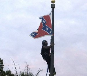 Bree Newsome of Charlotte, N.C., climbs a flagpole to remove the Confederate battle flag at a Confederate monument in front of the Statehouse in Columbia, S.C. (AP Image)