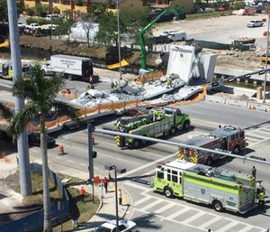 Several people were seen being loaded onto ambulances after at least five vehicles were trapped underneath the newly-installed bridge. (Photo/AP)