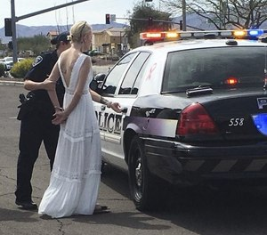 This photo provided by the Marana Police Department, in Arizona, shows 32-year-old Amber Young during her arrest on suspicion of impaired driving, Monday, March 12, 2018, in southern Arizona. Police say Young became involved in a car crash in Marana as she was driving to her wedding. One person suffered minor injuries in the three-vehicle crash. (Marana Police Department via AP)