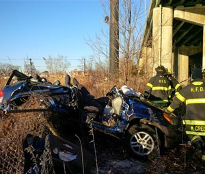 In this photo provided by the Hackensack Fire Department, firefighters work the scene of an accident near an overpass along Route 80 in Hackensack, N.J., Friday, Feb. 13, 2015. An SUV driver swerving to avoid striking another vehicle on the highway hit a snowbank along a guardrail and catapulted 60 feet off a bridge. Incredibly, authorities say, the two occupants suffered only minor injuries, and the vehicle landed upright. (AP Photo/Hackensack Fire Department, Justin Derevyanik)