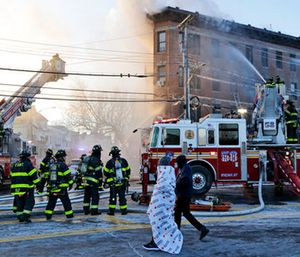 Firefighters work to contain a blaze at a building in the Bronx section of New York. (AP Photo/Seth Wenig)