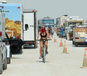 In this Aug. 26, 2013 file photo, a woman rides her bike between cars waiting to enter Burning Man in Gerlach, Nev. (Andy Barron/Reno Gazette-Journal via AP)