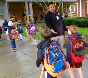 In this Nov. 6, 2017 photo, campus monitor Hector Garcia greets students as they got off the bus at the start of the school day at West Elementary School in New Canaan, Conn. (AP Photo/Michael Melia)