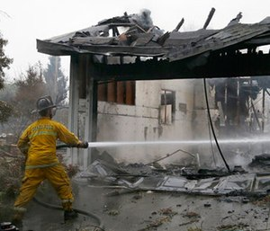 A Santa Rosa firefighter hoses down a hotspot in the Coffey Park area of Santa Rosa, Calif. (AP Photo/Ben Margot)