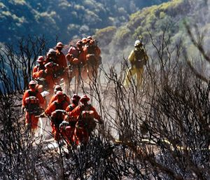 CAL FIRE Inmate Firefighting Hand Crew members hike through the charred landscape on their way to work east of Gibraltar Road above Montecito, Calif. (Mike Eliason/Santa Barbara County Fire Department via AP)