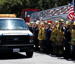 Firefighters salute as a van carrying the body of Long Beach Fire Capt. Dave Rosa passes them during a procession. (AP Photo/Jae C. Hong)