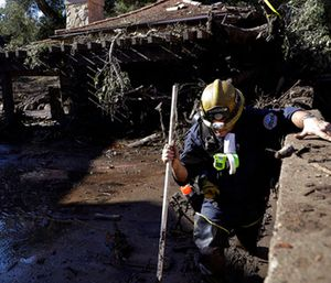 Alex Broumand of the Montecito Fire Department walks in mud in front of homes damaged from storms in Montecito, Calif. (AP Photo/Marcio Jose Sanchez)