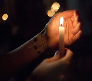 Randi Landry, of Lafayette, holds a candle during a vigil to honor the victims of Thursday night's shooting at The Grand 16 theater Friday, July 24, 2015, in Lafayette, La. (AP Image)